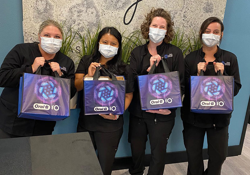 staff members holding Oral-B gift bags